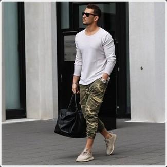Wie kombinieren: weißer Pullover mit einem Rundhalsausschnitt, olivgrüne Camouflage Jogginghose, hellbeige niedrige Sneakers, schwarze Leder Reisetasche