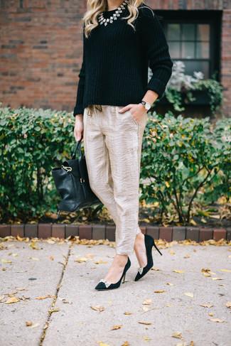 Wie kombinieren: schwarzer Pullover mit einem Rundhalsausschnitt, hellbeige Karottenhose aus Seide, schwarze verzierte Wildleder Pumps, schwarze Satchel-Tasche aus Leder