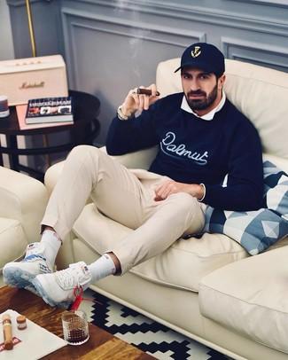 Wie kombinieren: dunkelblauer bedruckter Pullover mit einem Rundhalsausschnitt, weißes Langarmhemd, hellbeige Chinohose, weiße Sportschuhe