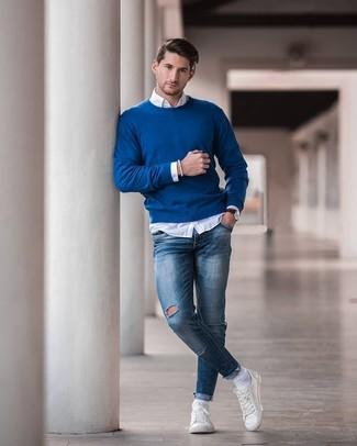 Wie kombinieren: blauer Pullover mit einem Rundhalsausschnitt, weißes Langarmhemd, blaue enge Jeans mit Destroyed-Effekten, weiße Leder niedrige Sneakers