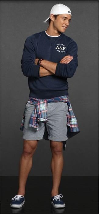 Wie kombinieren: dunkelblauer Pullover mit einem Rundhalsausschnitt, blaues Langarmhemd mit Schottenmuster, graue Shorts, dunkelblaue niedrige Sneakers