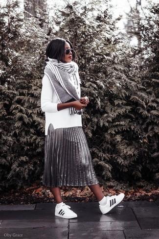 Wie kombinieren: weißer Pullover mit einem Rundhalsausschnitt, silberner Falten Midirock, weiße und schwarze Leder niedrige Sneakers, grauer vertikal gestreifter Schal