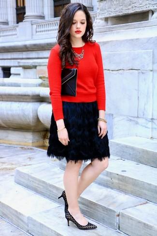 Wie kombinieren: roter Pullover mit einem Rundhalsausschnitt, schwarzer Fransen Minirock, schwarze gepunktete Wildleder Pumps, schwarze Leder Clutch