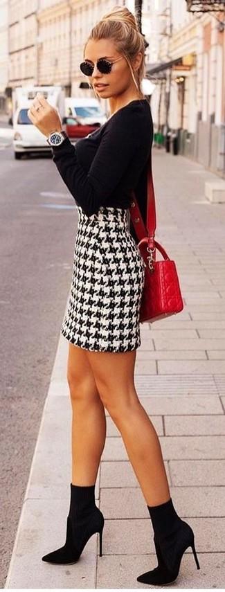 Wie kombinieren: schwarzer Pullover mit einem Rundhalsausschnitt, weißer und schwarzer Minirock mit Hahnentritt-Muster, schwarze elastische Stiefeletten, rote gesteppte Leder Umhängetasche