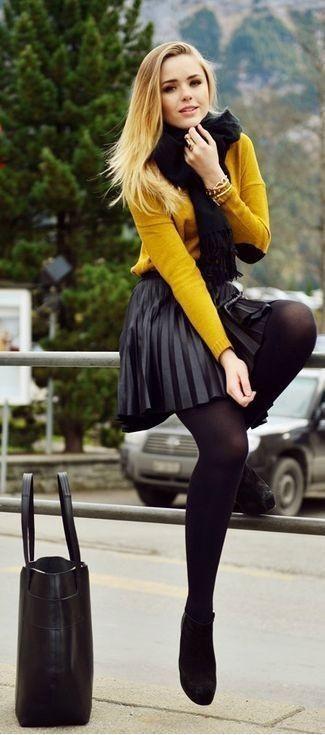 Wie kombinieren: senf Pullover mit einem Rundhalsausschnitt, schwarzer Falten Leder Minirock, schwarze Wildleder Stiefeletten, schwarze Shopper Tasche aus Leder