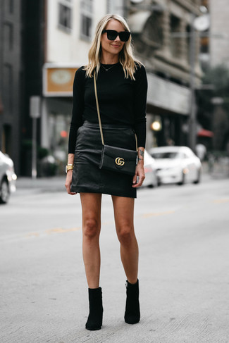 Wie kombinieren: schwarzer Pullover mit einem Rundhalsausschnitt, schwarzer Leder Minirock, schwarze Wildleder Stiefeletten, schwarze Leder Umhängetasche