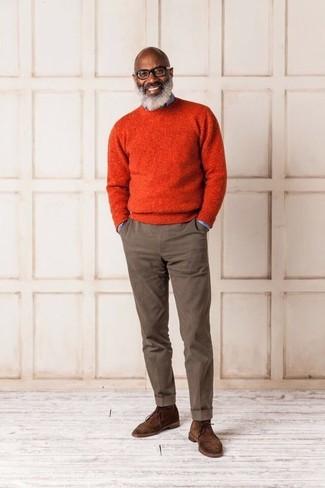 Wie kombinieren: orange Pullover mit einem Rundhalsausschnitt, hellblaues Jeanshemd, braune Chinohose, braune Chukka-Stiefel aus Wildleder