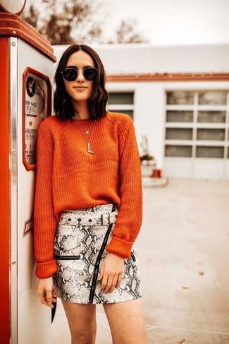 Wie kombinieren: orange Pullover mit einem Rundhalsausschnitt, grauer Leder Minirock mit Schlangenmuster, schwarze und goldene Sonnenbrille, goldener Anhänger