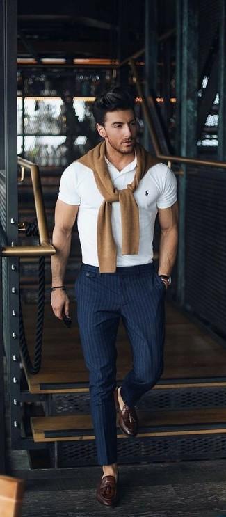 Wie kombinieren: beige Pullover mit einem Rundhalsausschnitt, weißes Polohemd, dunkelblaue vertikal gestreifte Anzughose, dunkelbraune Leder Slipper mit Quasten