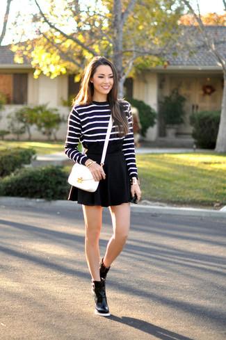 Wie kombinieren: schwarzer und weißer horizontal gestreifter Pullover mit einem Rundhalsausschnitt, schwarzer Skaterrock, schwarze Leder Stiefeletten, weiße Leder Umhängetasche