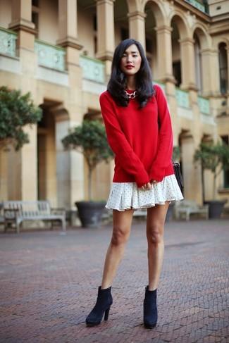 Wie kombinieren: roter Pullover mit einem Rundhalsausschnitt, weißes gepunktetes schwingendes Kleid, dunkelblaue Wildleder Stiefeletten, schwarze Leder Umhängetasche