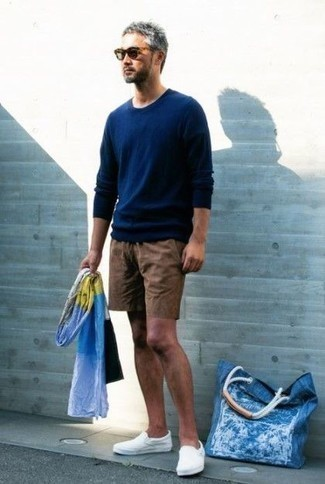 Weiße Slip-On Sneakers aus Segeltuch kombinieren – 54 Herren Outfits: Kombinieren Sie einen dunkelblauen Pullover mit einem Rundhalsausschnitt mit braunen Shorts für ein Alltagsoutfit, das Charakter und Persönlichkeit ausstrahlt. Weiße Slip-On Sneakers aus Segeltuch sind eine perfekte Wahl, um dieses Outfit zu vervollständigen.