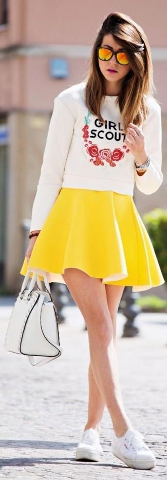 Wie kombinieren: weißer bedruckter Pullover mit einem Rundhalsausschnitt, gelber Skaterrock, weiße Leinenschuhe, weiße Satchel-Tasche aus Leder
