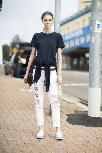 schwarzer Pullover mit einem Rundhalsausschnitt, schwarzes T-Shirt mit einem Rundhalsausschnitt, weiße Boyfriend Jeans mit Destroyed-Effekten, weiße niedrige Sneakers für Damen