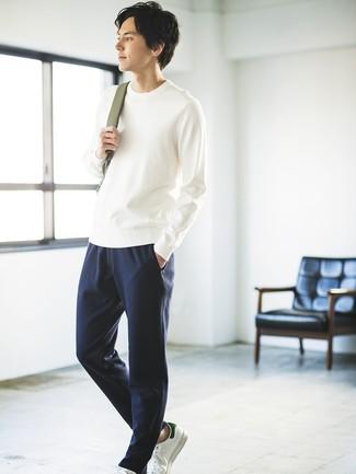 Wie kombinieren: weißer Pullover mit einem Rundhalsausschnitt, dunkelblaue Jogginghose, weiße Leder niedrige Sneakers, olivgrüner Rucksack