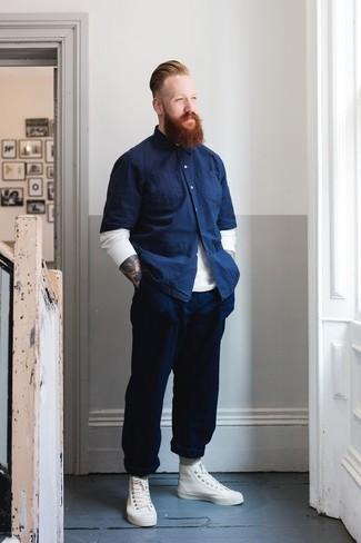 Wie kombinieren: weißer Pullover mit einem Rundhalsausschnitt, dunkelblaues Chambray Kurzarmhemd, dunkelblaue Chinohose, weiße hohe Sneakers aus Leder