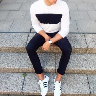 Wie kombinieren: weißer und schwarzer Pullover mit einem Rundhalsausschnitt, schwarze enge Jeans, weiße und schwarze Leder niedrige Sneakers, schwarze Lederuhr