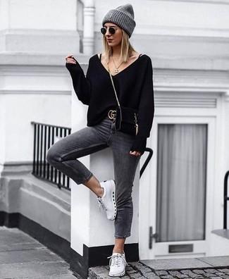 Wie kombinieren: schwarzer Pullover mit einem V-Ausschnitt, dunkelgraue enge Jeans, weiße niedrige Sneakers, schwarze Wildleder Umhängetasche