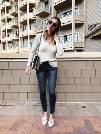 Wie kombinieren: hellbeige Pullover mit einem V-Ausschnitt, schwarze enge Jeans mit Destroyed-Effekten, hellbeige Wildleder Slipper, graue Leder Umhängetasche