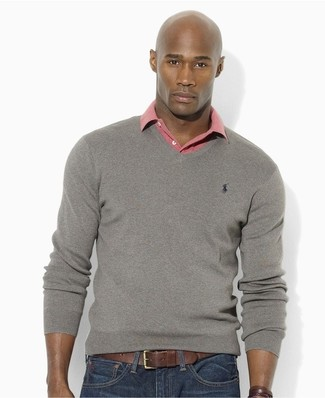 Wie kombinieren: grauer Pullover mit einem V-Ausschnitt, rosa Polohemd, dunkelblaue enge Jeans, schwarzer Ledergürtel