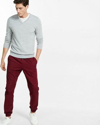 Wie kombinieren: grauer Pullover mit einem V-Ausschnitt, weißes T-Shirt mit einem Rundhalsausschnitt, dunkelrote Chinohose, weiße Leder niedrige Sneakers