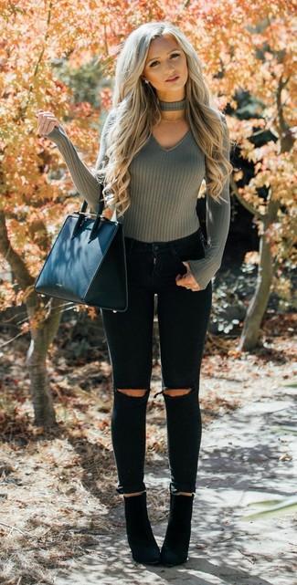 Wie kombinieren: olivgrüner Pullover mit einem V-Ausschnitt, schwarze enge Jeans mit Destroyed-Effekten, schwarze Wildleder Stiefeletten, schwarze Shopper Tasche aus Leder
