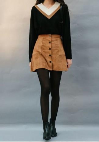 Wie kombinieren: schwarzer Pullover mit einem V-Ausschnitt, brauner Wildlederrock mit knöpfen, schwarze Chelsea-Stiefel aus Leder, schwarze Wollstrumpfhose