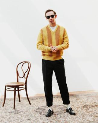 Herren Outfits 2021: Paaren Sie einen gelben Pullover mit einem V-Ausschnitt mit einer schwarzen Chinohose für ein Alltagsoutfit, das Charakter und Persönlichkeit ausstrahlt. Fühlen Sie sich ideenreich? Komplettieren Sie Ihr Outfit mit schwarzen Leder Slippern.