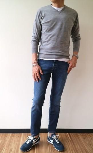 Wie kombinieren: grauer Pullover mit einem V-Ausschnitt, weißes T-Shirt mit einem Rundhalsausschnitt, dunkelblaue enge Jeans, dunkelblaue Wildleder niedrige Sneakers