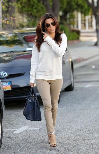 Wie kombinieren: weißer Pullover mit einem V-Ausschnitt, hellbeige enge Jeans, silberne Leder Sandaletten, schwarze Shopper Tasche aus Leder
