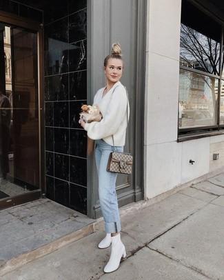 Wie kombinieren: weißer Pullover mit einem V-Ausschnitt, hellblaue Jeans, weiße Leder Stiefeletten, hellbeige bedruckte Satchel-Tasche aus Segeltuch