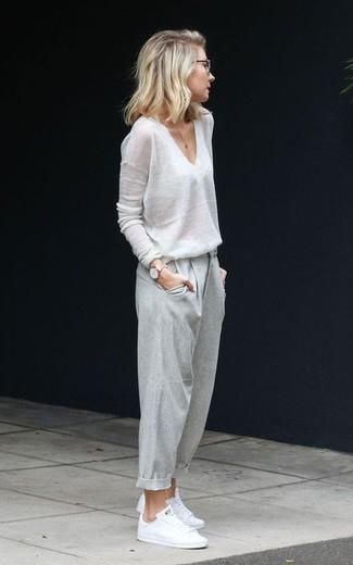 Wie kombinieren: weißer Pullover mit einem V-Ausschnitt, graue Karottenhose, weiße niedrige Sneakers, goldene Uhr