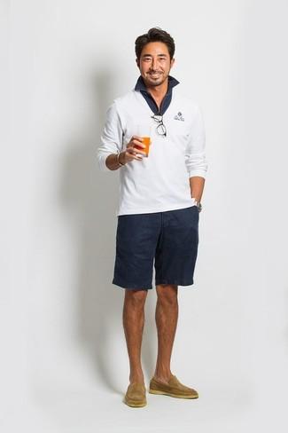 Wie kombinieren: weißer Pullover mit einem V-Ausschnitt, dunkelblaues Polohemd, dunkelblaue Shorts, beige Wildleder Slipper