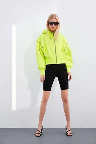 Wie kombinieren: gelbgrüner Pullover mit einer Kapuze, schwarze Radlerhose, schwarze Leder Sandaletten, schwarze Sonnenbrille