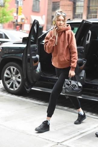 Wie kombinieren: orange Pullover mit einer Kapuze, schwarze Jogginghose, schwarze Sportschuhe, schwarze Shopper Tasche aus Leder