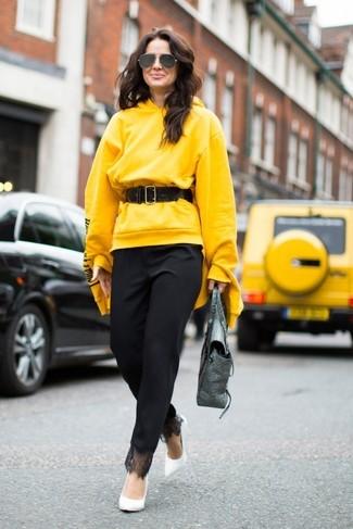 Wie kombinieren: gelber Pullover mit einer Kapuze, schwarze Karottenhose, weiße Leder Pumps, silberne Satchel-Tasche aus Leder