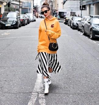 Wie kombinieren: orange Pullover mit einer Kapuze, weißes und schwarzes vertikal gestreiftes Midikleid, weiße Leder Stiefeletten, schwarze Leder Umhängetasche