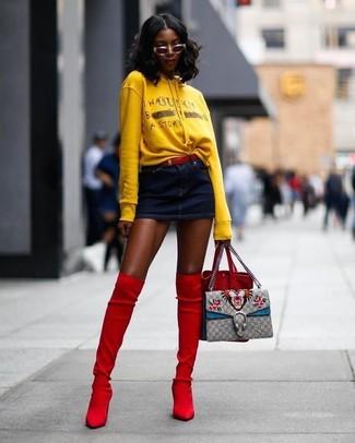 Wie kombinieren: gelber bedruckter Pullover mit einer Kapuze, dunkelblauer Jeans Minirock, rote Overknee Stiefel aus Wildleder, rote Wildleder Beuteltasche