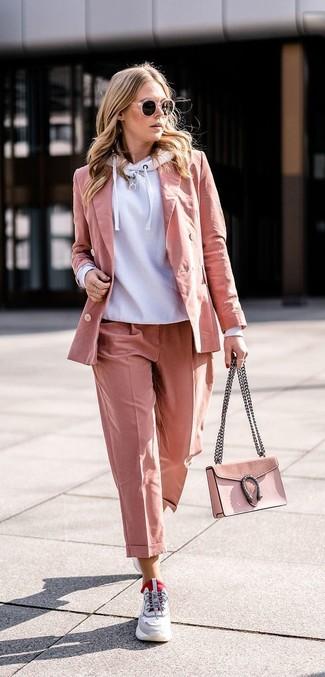 Wie kombinieren: grauer Pullover mit einer Kapuze, rosa Sakko, rosa Anzughose, graue Sportschuhe