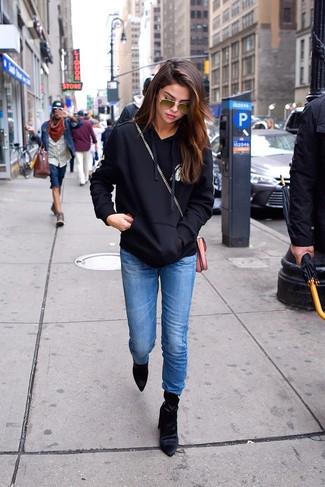 Wie kombinieren: schwarzer und weißer bedruckter Pullover mit einer Kapuze, blaue Jeans, schwarze Samt Stiefeletten, rosa Leder Umhängetasche