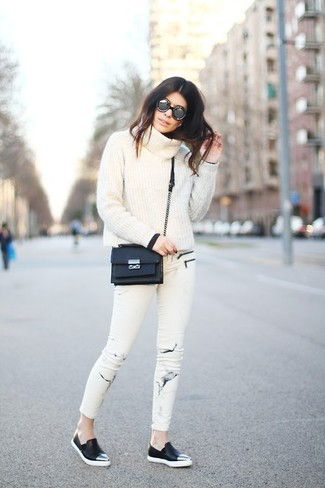Wie kombinieren: weißer Pullover mit einer weiten Rollkragen, weiße bedruckte enge Jeans, schwarze Slip-On Sneakers aus Leder, schwarze Leder Umhängetasche