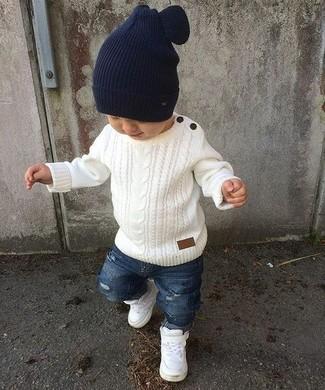 Wie kombinieren: weißer Pullover, blaue Jeans mit Destroyed-Effekten, weiße Turnschuhe, dunkelblaue Mütze