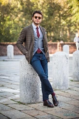 Dunkelbraune Doppelmonks aus Leder kombinieren: trends 2020: Kombinieren Sie einen grauen Pullunder mit dunkelblauen Jeans für Drinks nach der Arbeit. Heben Sie dieses Ensemble mit dunkelbraunen Doppelmonks aus Leder hervor.