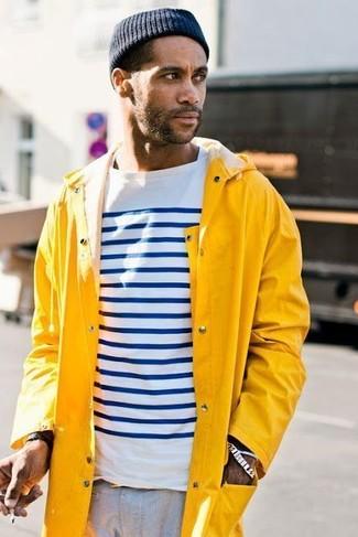 Wie kombinieren: gelbe Regenjacke, weißes und dunkelblaues horizontal gestreiftes Langarmshirt, graue Chinohose, dunkelblaue Mütze