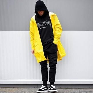 Wie kombinieren: gelbe Regenjacke, schwarzer und weißer bedruckter Pullover mit einem Kapuze, schwarze Jogginghose, schwarze Wildleder niedrige Sneakers