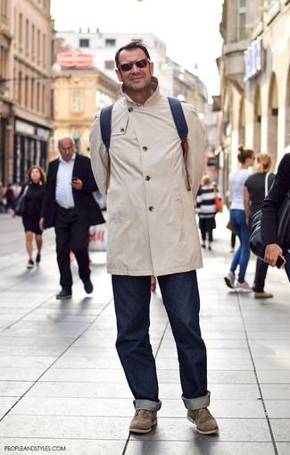 Wie kombinieren: hellbeige Regenjacke, dunkelblaue Jeans, olivgrüne Chukka-Stiefel aus Wildleder, schwarzer Leder Rucksack