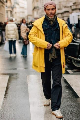 Wie kombinieren: gelbe Regenjacke, dunkelblaue Jeansjacke, schwarze Chinohose, hellbeige Wildleder niedrige Sneakers