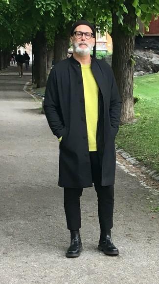 Wie kombinieren: schwarze Regenjacke, gelbgrüner Pullover mit einem Rundhalsausschnitt, schwarze Chinohose, schwarze Chelsea-Stiefel aus Leder