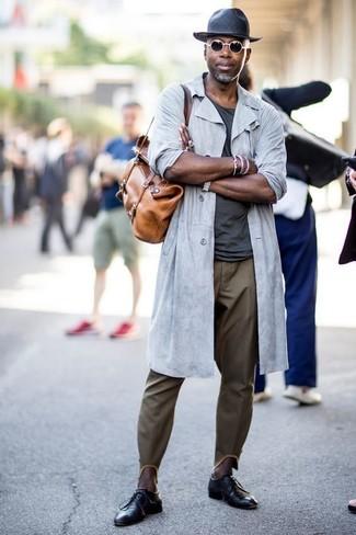 Wie kombinieren: graue Regenjacke, dunkelgraues T-Shirt mit einem Rundhalsausschnitt, olivgrüne Chinohose, schwarze Leder Derby Schuhe