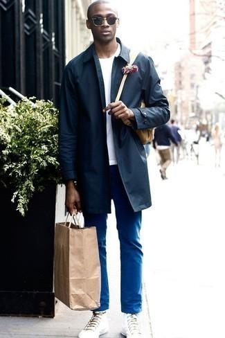 Herren Outfits & Modetrends 2020: Die Kombination von einer dunkelblauen Regenjacke und einer blauen Chinohose erlaubt es Ihnen, Ihren Freizeitstil klar und einfach zu halten. Wählen Sie die legere Option mit weißen hohen Sneakers aus Segeltuch.